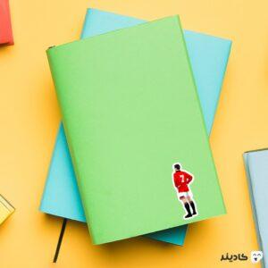 استیکر لپ تاپ اریک کانتونا روی دفترچه